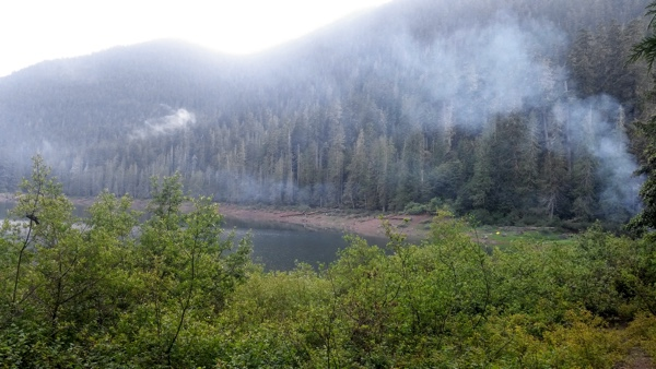 Campfire smoke rises lazily over the lake on a rainy Saturday afternoon.
